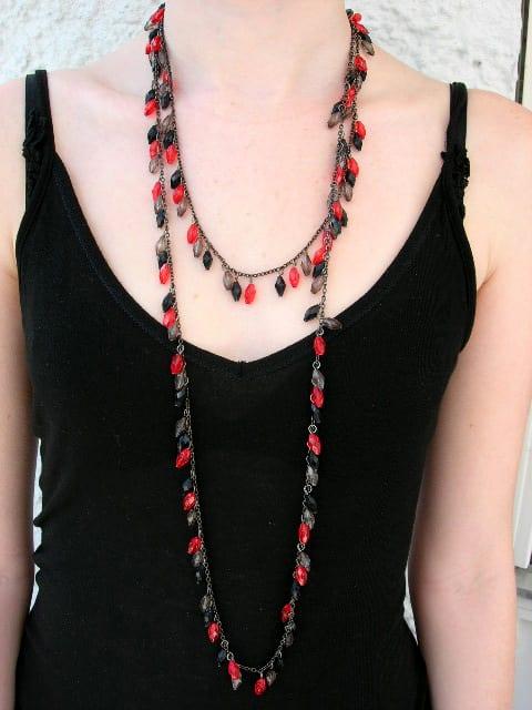 Långt halsband med grå, svarta o röda pärlor